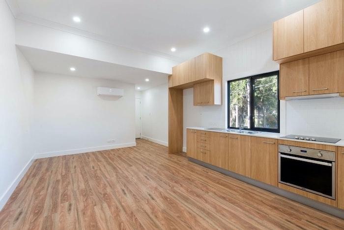 une cuisine avec des placards en bois claire et un four integré