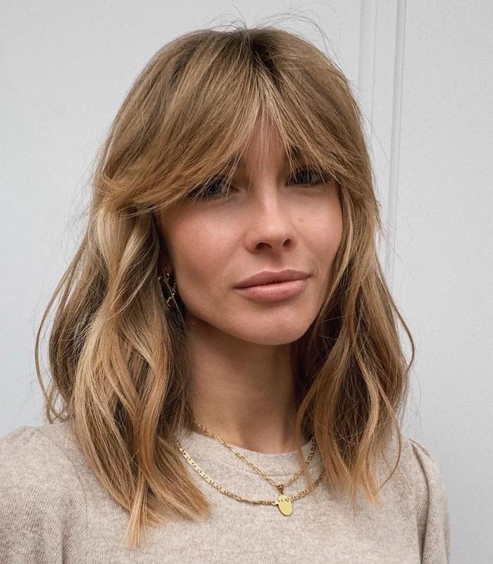 une femme a cheveux blondes foncés et un pull beige porte un fringe rideau