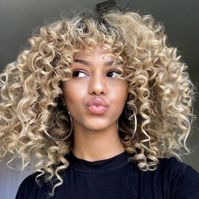 une femme afro avec des cheveux bouclés des grandes créoles sur les oreilles et coiffure frange