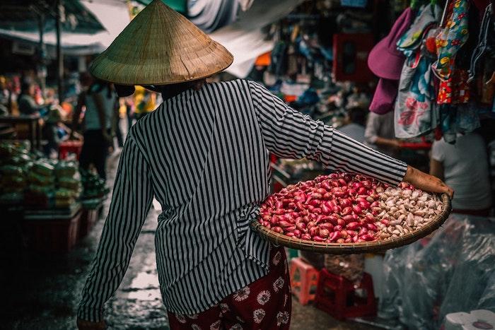 une femme avec chapeau en rotin marche pour legumes et fruits