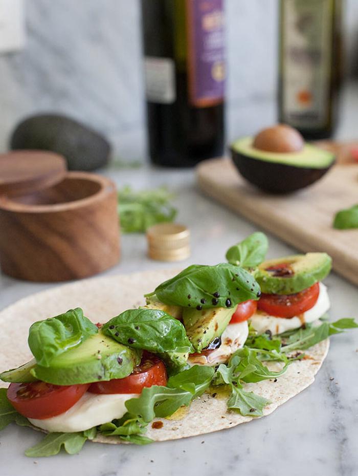 une image qui montre comment plier un wrap avec de mozzarella tomates et de l avocat