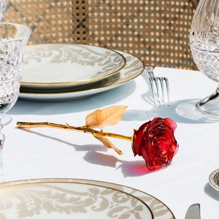 une rose cristal sur une table mis pour diner avec des assiettes en porcelaine