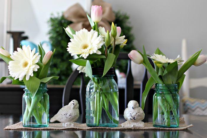 vase en bocal et pot de fleur sur un chemin de table en jute et des figurines d oiseaux originales, déco de printemps pour table