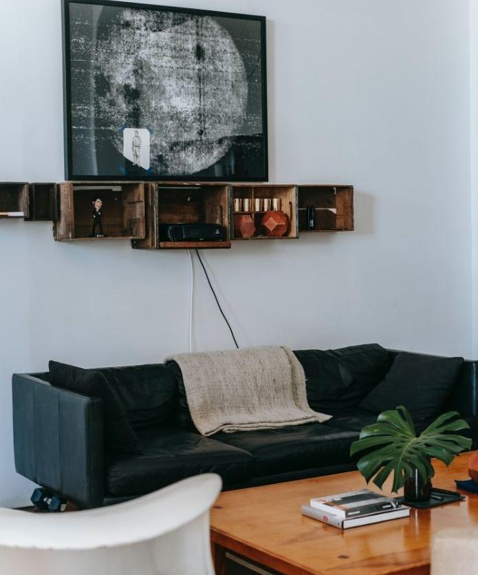 étageres récup industrielles murales dans salon style industriel avec canapé noir de cuir et table basse bois