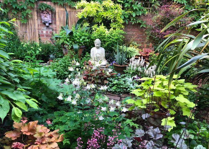 aménagement jardin zen avec pleine de végétation florissante pots de plantes mur de briques statuette bouddha