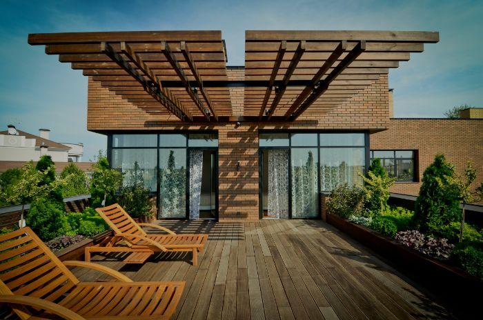 aménagement terrasse appartement boisée avec pergola en bois chaise longues et petit jardin en longueur