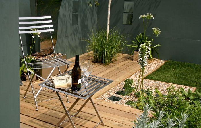 aménager sa terrasse en bois avec chaise et table metallique bordure gravier gazon vert buis autres plantes vertes
