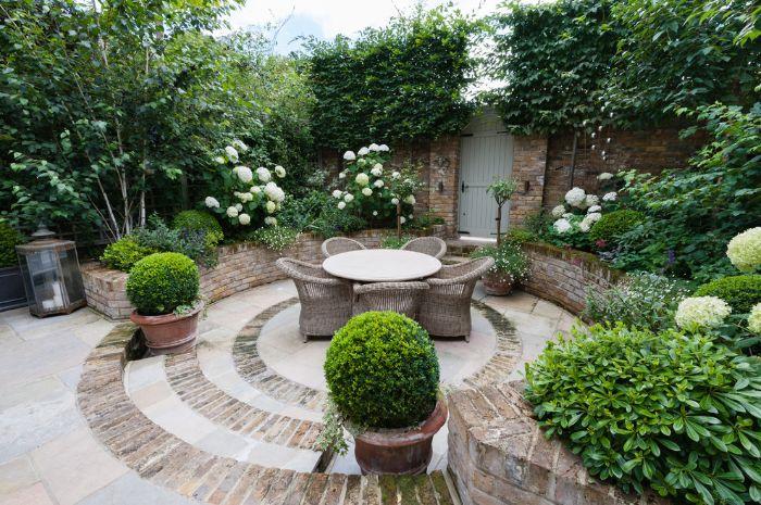 aménager sa terrasse extérieure en dalles et pierre salon de jardin rotin et table ronde vegetation tout autour plantes vertes et buis