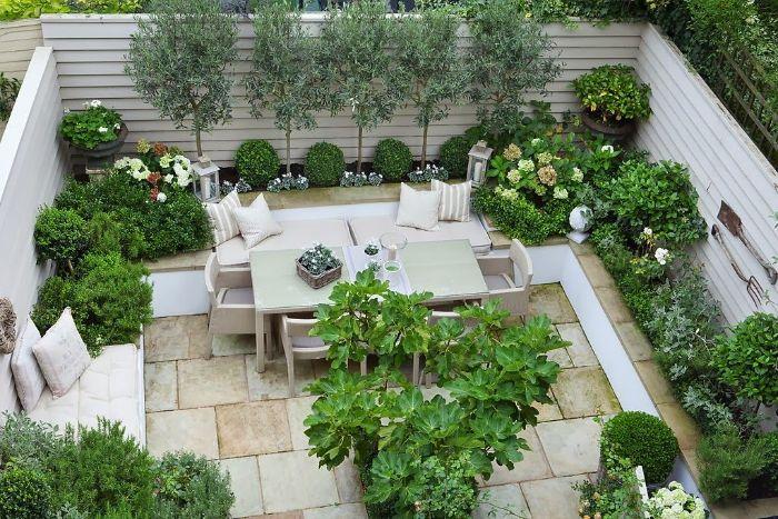 aménager une terrase extérieure en dalles de pierre salon de jardin entouré de végétation verte buis et arbres