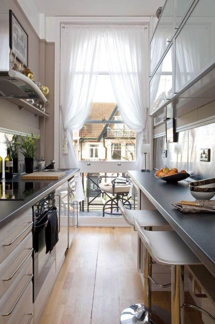 aménagement d une cuisine en longueur avec un comptior des chaises de bar et une vue sur la rue