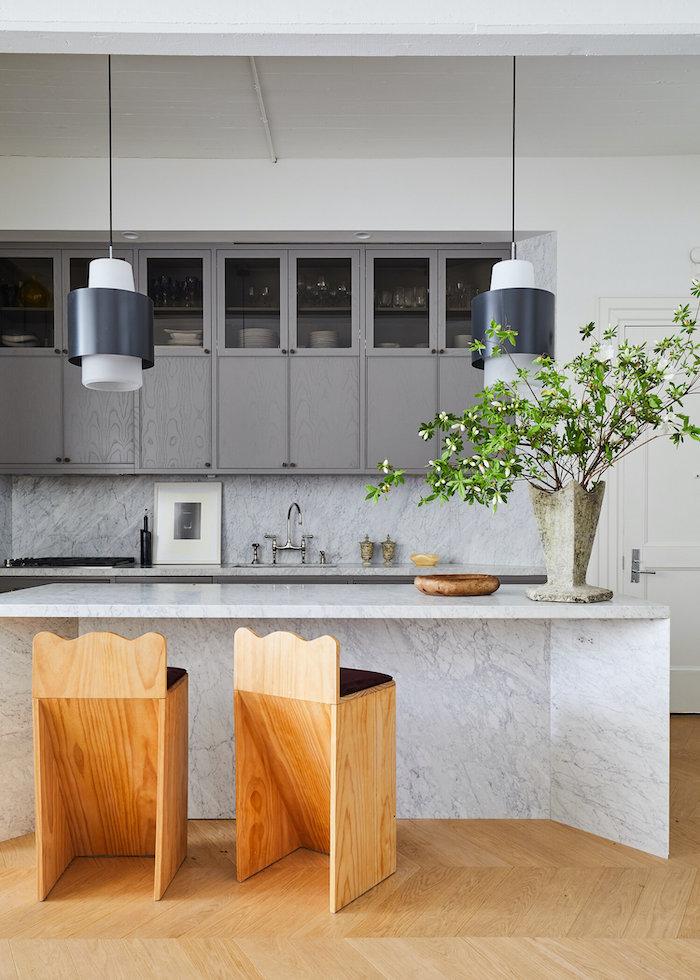 aménager petite cuisine fermée avec un bar en marbre et deux chaises en bois modernes
