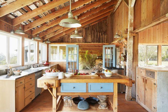 amenagement cuisine style campagne chic avec poutres apparentes et murs de bois ilot central table meuble bois vaisselle ustensiles exposés