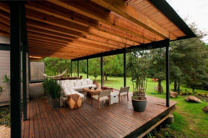 amenagement terrasse bois avec salon de terrasse avec table chaises et canapé couverture pergola et plantes exotiques