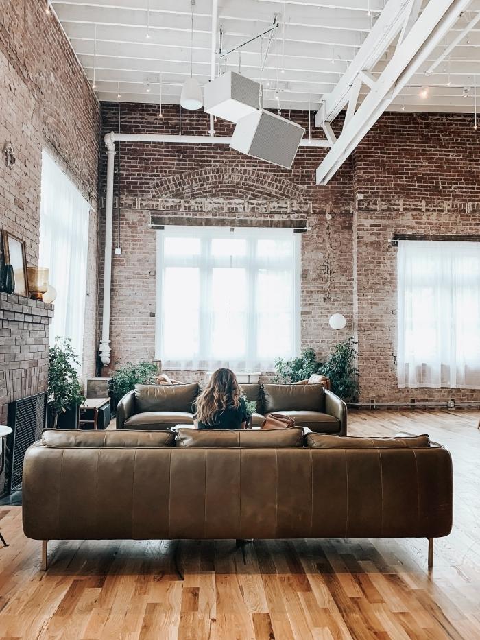 appartement style industriel canapé club cuir marron parquet sol stratifié cheminée fer mur briques