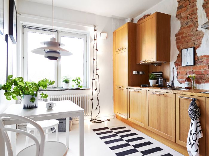 astuce amenager petite cuisine fermée de bois avec credence brique et peinture blanche tapis zebre table et chaises blanches