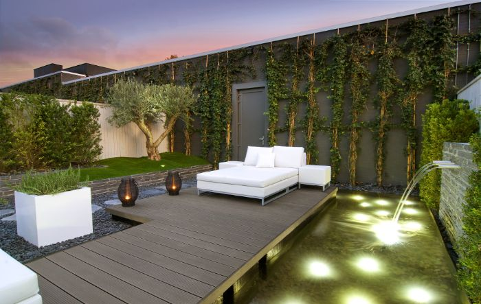 bassin de jardin mur végétalisé pont de bois terrasse avec canapé blanc chemin de pierre banc de bois.jfif