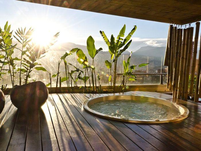 bordure de plantes vertes exotiques jaccuzzi privatif sur terrasse couverte moderne avec rideau bambou