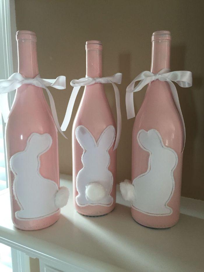 bouteilles de vin recyclées peintes de peinture rose avec motig lapin blanc à queue en coton et ruban blanc