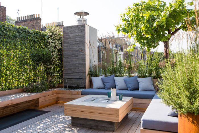 brise vue de jardin mur végétal canapé d angle avec coussin d assise grise table bois plantes vertes d exterieur