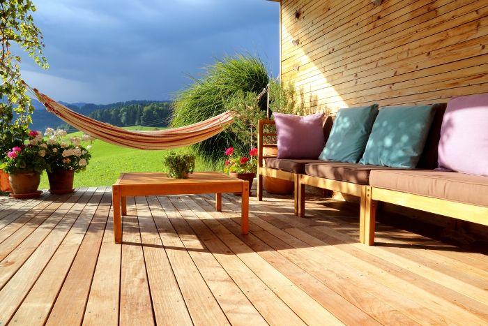 canapé de bois couvert de housses d assise et de coussins coloréstable basse bois amenagement terrasse devant maison