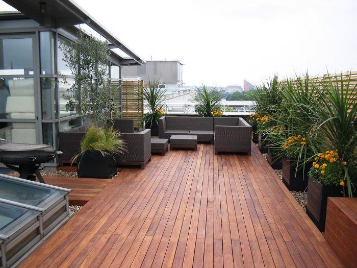 canapé et table exterieur en resine sur terrasse de bois avec des bacs à flurs bois et plantes à l intérieur terrasse de toit