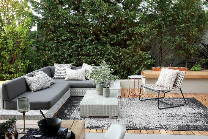canapé et table résinte blanche assises blanches chaise tressée et métal terrasse revêtement bois arbres vegetation
