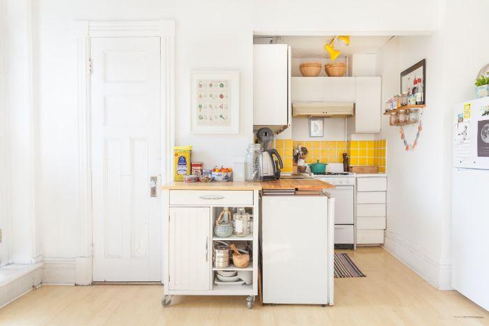 carrelage jaune dans petite cuisine ouverte en l avec pkan de travail bois sur meuble blanc ilot central amovible sur roulettes