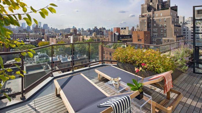 chaise longues de bois sur terrasse avec des pots jardinières remplies de fleurs et des serviettes à rayures