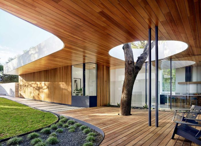 chaise longues sur terrasse bois couleur noire et arbre cailloux noirs pelouse idée maison moderne idee amenagement terrasse