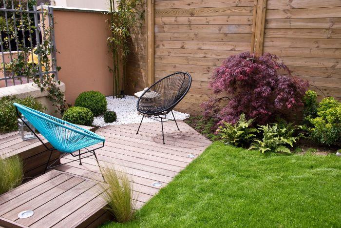 chaises en metal design sur une terrasse en bois dans un coin de jardin habiléde gazon et quelques plantes amenagement exterieur exemple