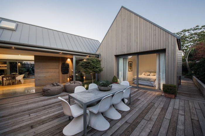 chambre ouverte sur terrasse en bois avec des chaises design blanches et plantes vertes en pot exterieur maison