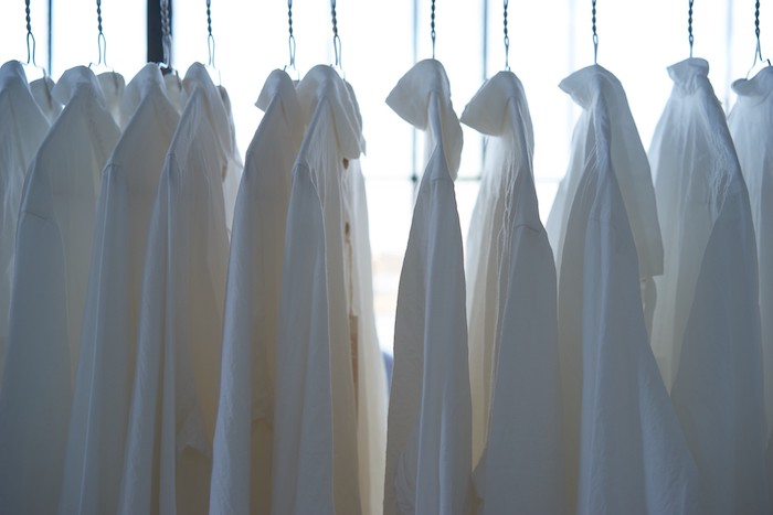 chemises blanches suspendu et rangés dans une armoire style minimaliste tenue chic femme