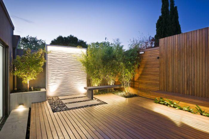 cloture de bois avec bambou dans un angle banc de bois galets terrasse deco exterieur maison éclairage nuit