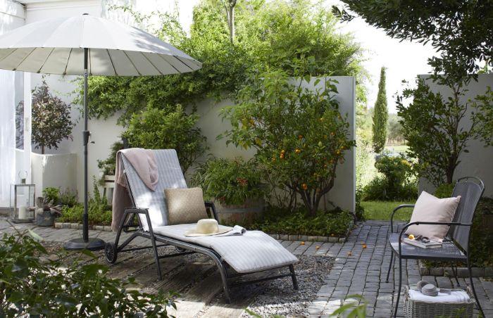 coin detente exterieur bordure de jardin vert avec des arbres fruitiers chemin de planches et gravier pavés de pierre
