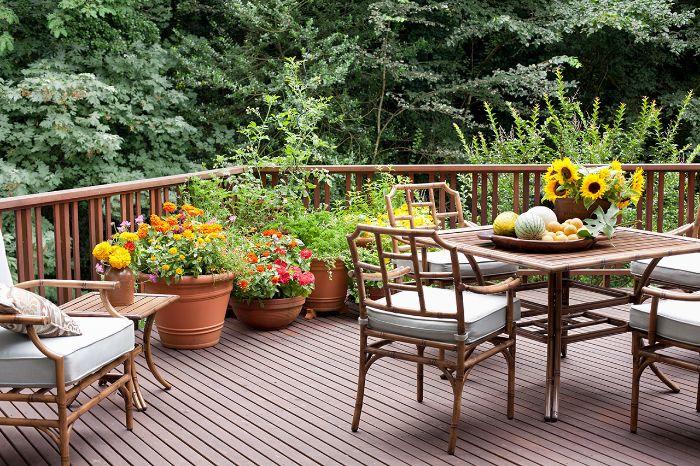 comment aménager sa terrasse en bois composite avec gros pots de fleurs chauses et table bois