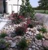comment décorer son espace devant maison avec un massif de fleurs avec des pierres en couleurs differents
