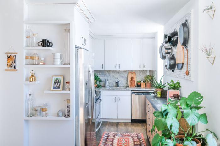 credence cuisine marbre et meubles hauts et bas blancs parquet bois clair panneau perforé blanc commode bois plan de travail noir tapis coloré