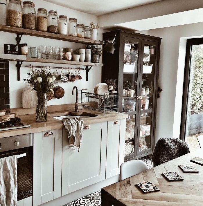 cuisine ancienne moderne avec meuble bois gris clair carrelage cerame vaisselier noir table et étagères ouvertes bois