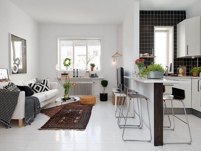 cuisine blanche carrelage noir ouverte sur un salon blanc séparation ilot de cuisine coussins plaids tapis orientaux