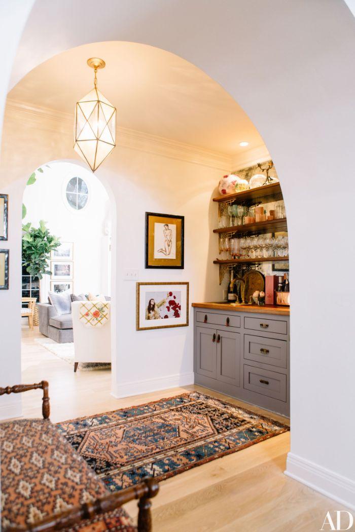 cuisine de bois avec plusieurs étagères ouvertes et des verres et tasses tapis coloré mur d art contemporain