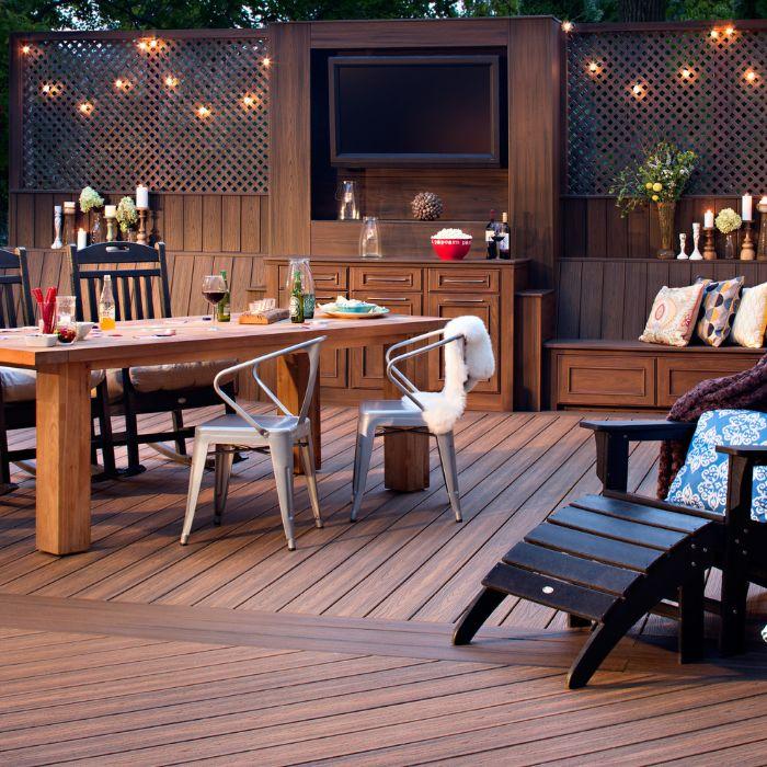 cuisine exterieure d été sur terrasse bois composite avec chaise longue et table bois et des chaises en métal