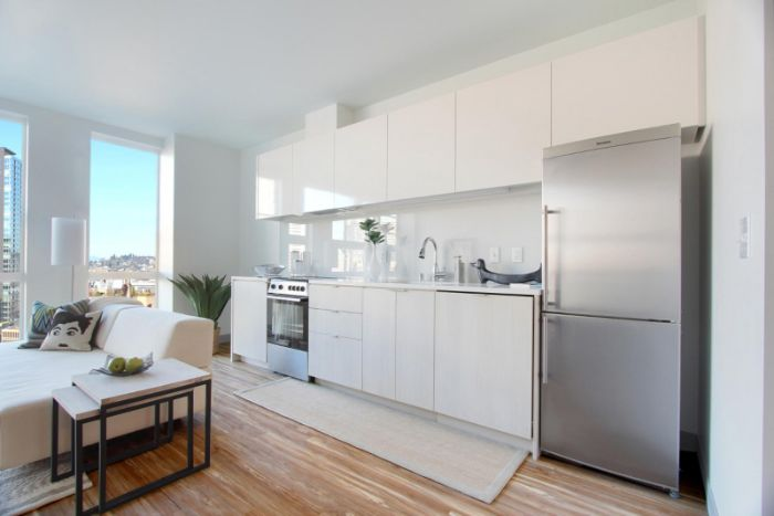 cuisine façade blanche frigon inox ouverte sur salon cocooning scandinave parquet bois clair