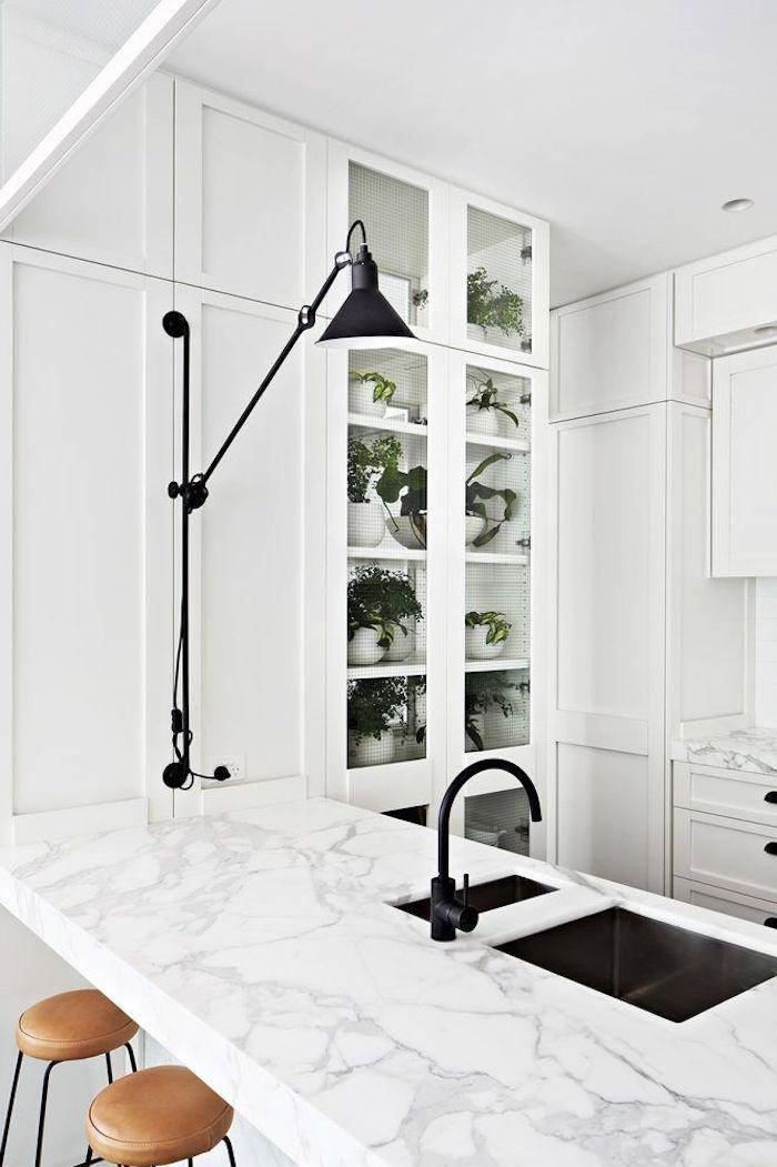 cuisine minimaliste en blanche et marbre avec une lampe de bureau et des placards en verre