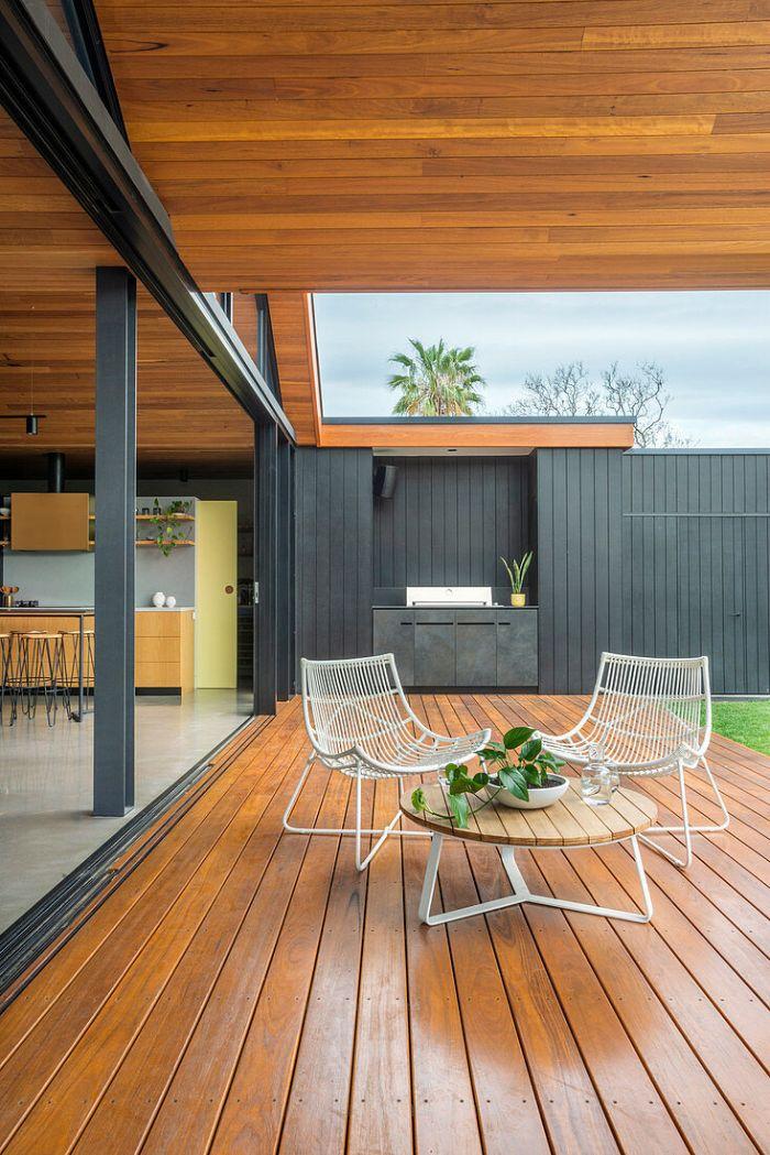 cuisine ouverte sur terrasse bois avec table bois et métal et chaises de metal blanches cuisine gris anthracite