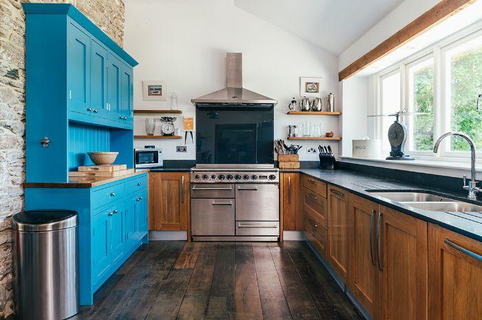 cuisine style campagne anglaise avec meuble bas bois poutre apparante parquet bois foncé armoire bleue murs blancs