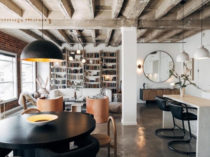 déco loft industriel avec plafond béton sol chaise noire table ronde mur en briques rouges bibliothèque