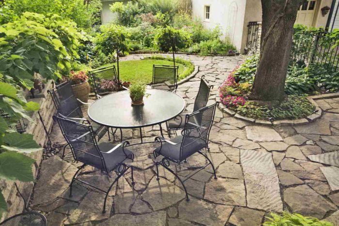 décoration de terrasse extérieure en pierre avec jardin avec arbres gazon bordure de plantes salon de jardin en table et chaises