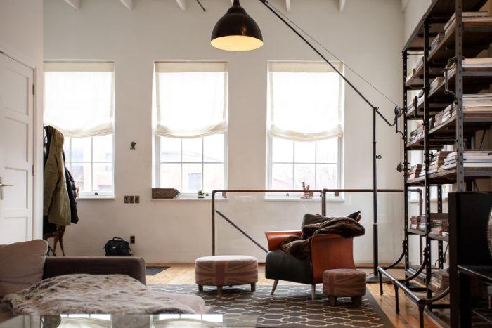 décoration industrielle de salon avec étagère livres en méta fauteuil marron cuir canapé gris murs blancs de loft.jfif