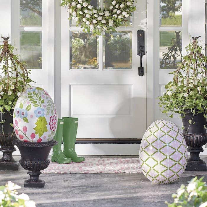 déco pâques extérieure avec des oeufs gigantesques décoratifs devant une maison blanche avec des bottes en caoutchouc