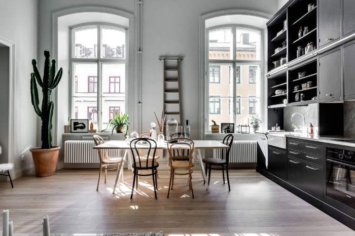 deco appartement haussmannien avec cuisine couleur noire ouverte sur salle à manger dans appartement parisien aux murs blancs